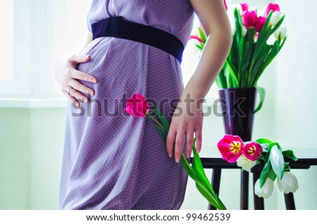 pregnant woman holding her tummy and tulip - stock photo