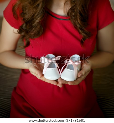 Pregnant woman holding little baby boots - stock photo