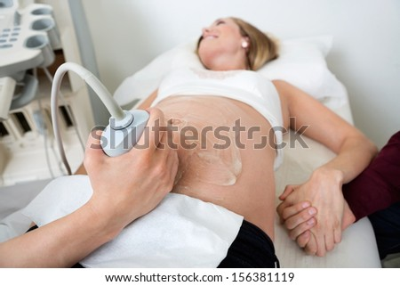 Pregnant woman holding man's hand while undergoing ultrasound scan in clinic - stock photo