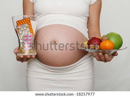 Pregnant woman holding medicine and fruits. Nine month. Third trimester - stock photo