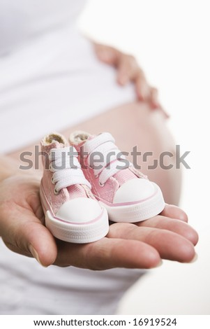 Pregnant woman holding pair of pink shoes for baby girl - stock photo
