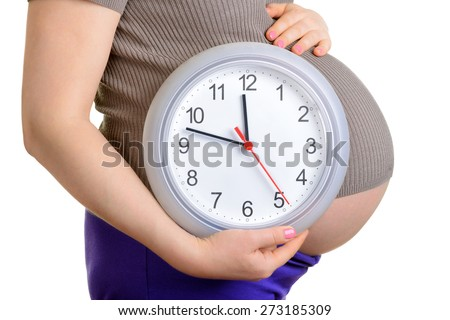 Pregnant woman holding wall clock. It's time. Isolated on white. - stock photo