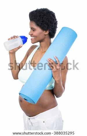 Pregnant woman holding water bottle and mat on white background - stock photo