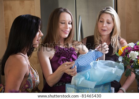 Pregnant woman holds baby clothes with friends in kitchen
