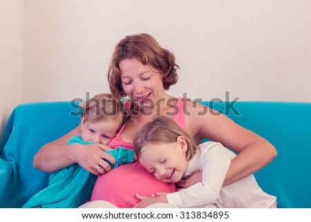Pregnant woman hugging his little daughters. Selective focus. - stock photo