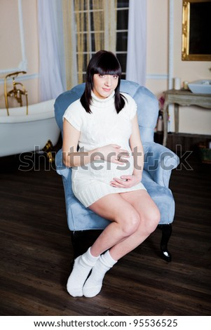 Pregnant woman in a sweater and socks sitting in a armchair