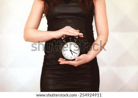 Pregnant woman in black dress with clock in her hands - stock photo