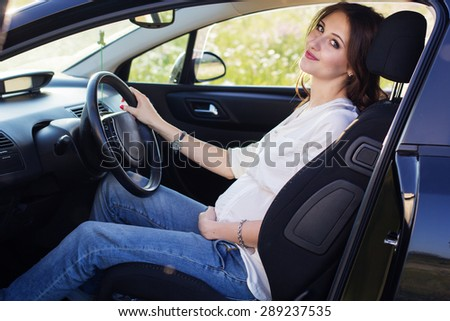 Pregnant woman in driving seat of the car - stock photo