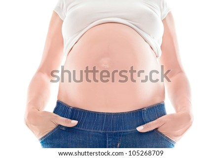 Pregnant woman in jeans demonstrating her belly. Closeup studio shot on white background