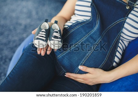 Pregnant woman in jeans knickers holding pair of small male shoes for baby (Shallow dof) - stock photo