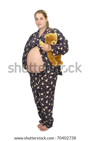 Pregnant woman in pajamas with teddy bear - stock photo
