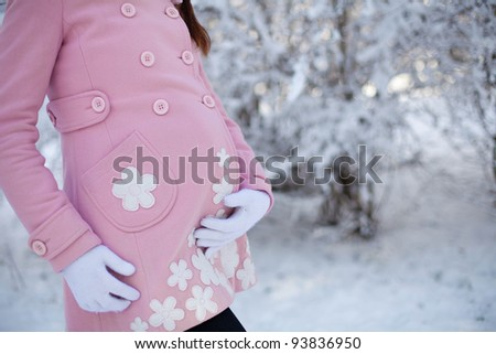 pregnant woman in snowy forest - stock photo
