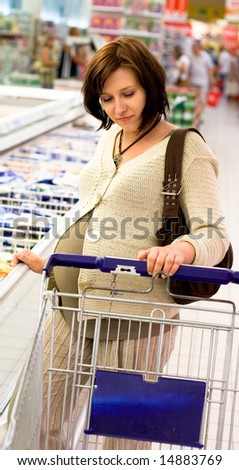 Pregnant woman in store - stock photo
