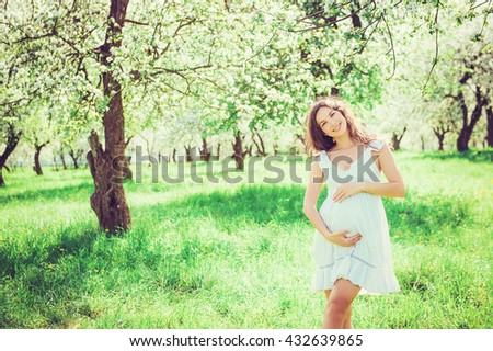 Pregnant woman in the apple orchard is holding tummy