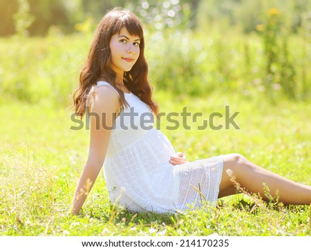 Pregnant woman in white dress in sunny summer day - stock photo
