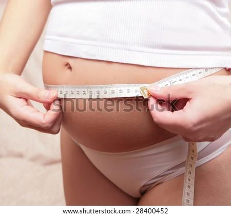 pregnant woman in white underwear measures tummy - stock photo