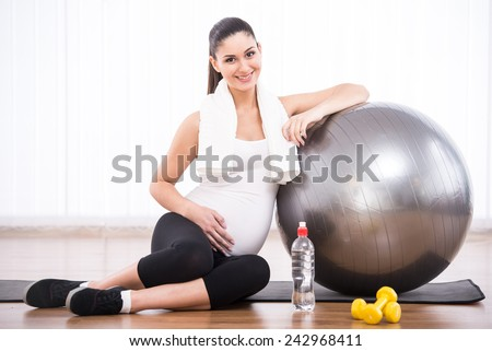 Pregnant woman is doing exercises with gymnastic ball. - stock photo