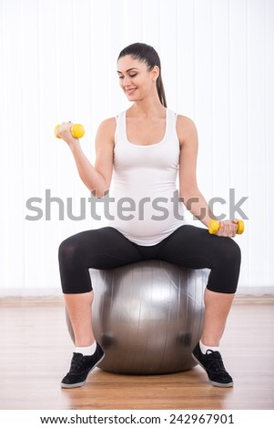 Pregnant woman is doing exercises with gymnastic ball and dumbbells. White background. - stock photo