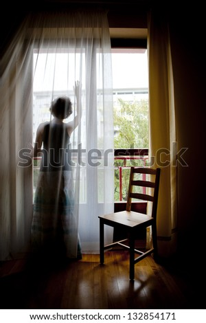 Pregnant woman is looking out of the window in her flat - stock photo