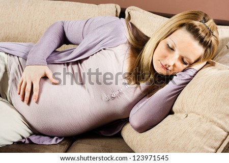 Pregnant woman is sleeping on sofa,Time for a nap - stock photo