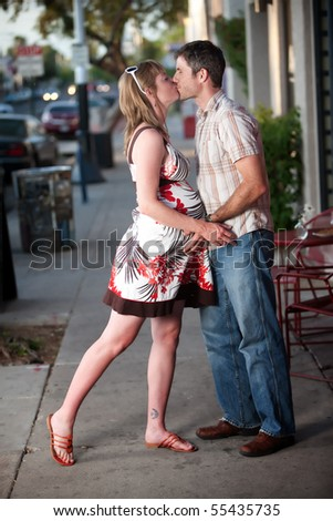 Pregnant woman kissed by her husband on the street - stock photo