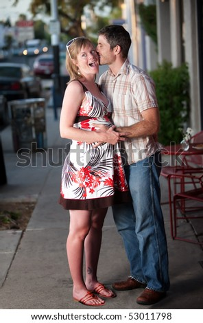 Pregnant woman kissed by her partner on the street - stock photo