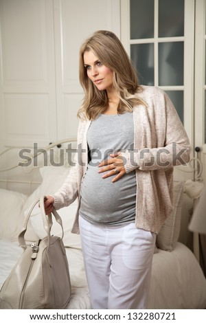 Pregnant woman leaving home holding away bag - stock photo