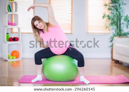 Pregnant woman looking at camera sitting on exercise ball in the living room - stock photo