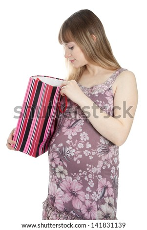 Pregnant woman looking in shopping bag - stock photo