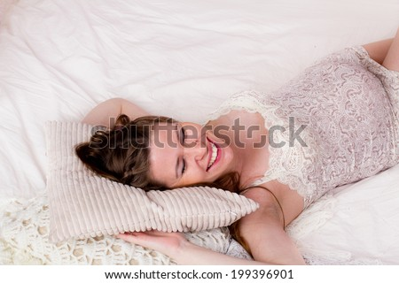 Pregnant woman lying in bed and smiling - stock photo
