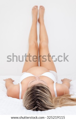 Pregnant woman lying on bed with legs raised up - stock photo