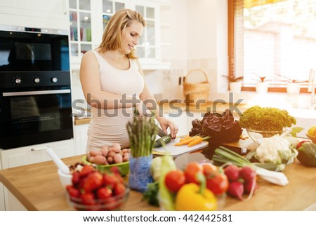 Pregnant woman making a meal in kitchen from fresh ingredients - stock photo
