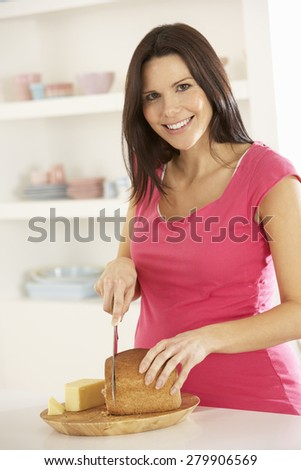 Pregnant Woman Making Sandwich In Kitchen At Home - stock photo