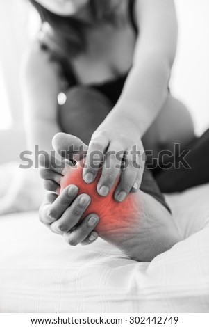 Pregnant woman massaging her painful foot, red highlighted on pain area - stock photo