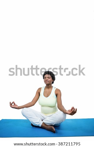 Pregnant woman meditating on mat on white backgroung