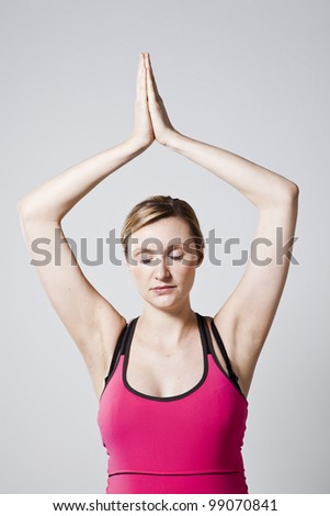 Pregnant woman meditating with hands together eyes closed