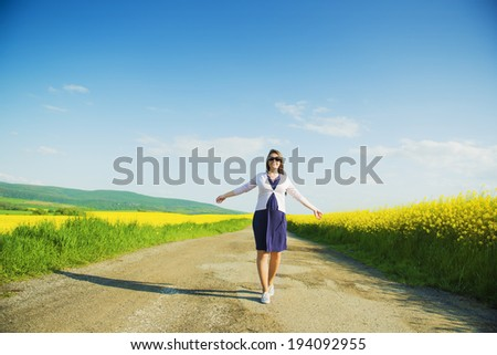 Pregnant woman on countryside road in the middle of yellow canola field - stock photo