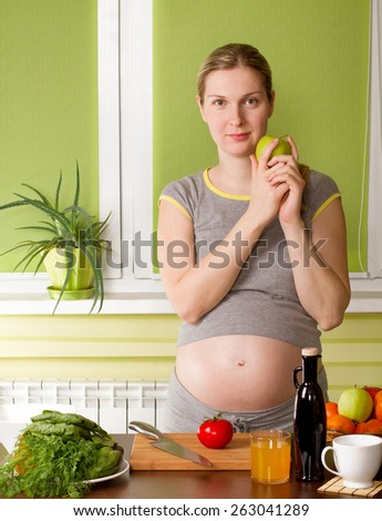 Pregnant woman on kitchen cooking healthy food - stock photo