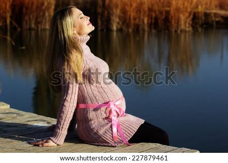 Pregnant woman on the autumn lake - stock photo
