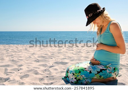 pregnant woman on the beach - stock photo