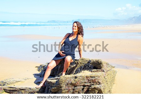 Pregnant woman on the beach at the atlantic ocean - stock photo