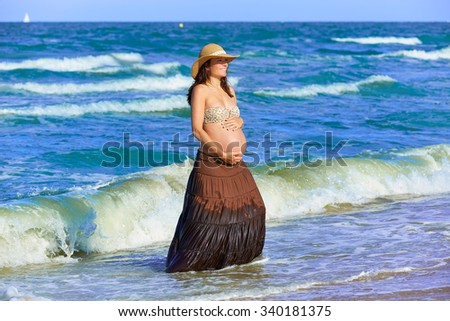 Pregnant woman on the beach playing with waves - stock photo