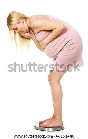 pregnant woman on the scales shoked - stock photo