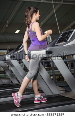 Pregnant woman on the treadmill in the gym - stock photo