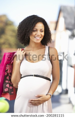 Pregnant woman out shopping - stock photo