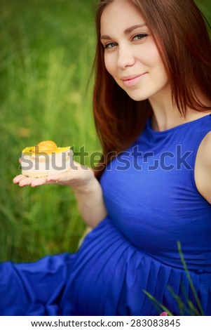 Pregnant woman Outdoors pregnant girl eating cake unhealthy eating pregnancy lady outdoors, pregnant female in park. soft focus, series - stock photo