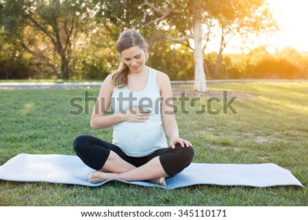 Pregnant woman outside in nature doing yoga - stock photo