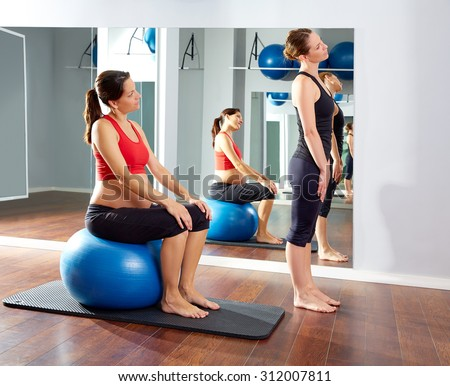 pregnant woman pilates exercise fitball at gym with personal trainer - stock photo