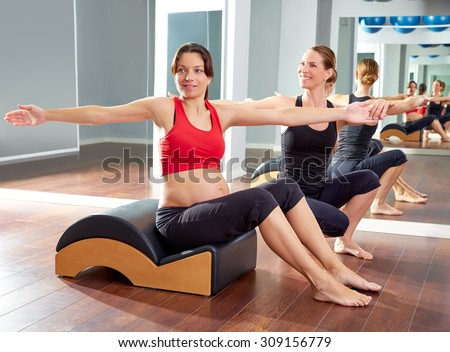 pregnant woman pilates exercise spine twist with Wave corrector and personal trainer - stock photo