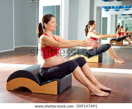 pregnant woman pilates exercise with spine wave corrector - stock photo